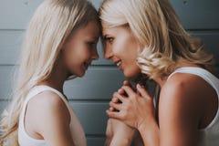 Blondynki matki spojrzenia w oczy blondynki córka, ściska ręki na drewnianym tle zdjęcie royalty free