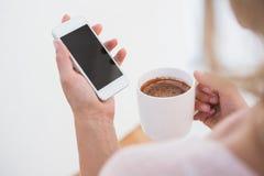 Blondynki mienia smartphone i kubek gorąca czekolada Obraz Royalty Free