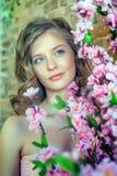 Blondynki nastoletnia dziewczyna blisko kwitnie drzewa Zdjęcie Royalty Free