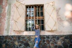 Blondynki nastoletnia dziewczyna w pasiastej bluzce blisko okno obraz stock