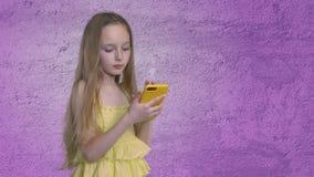 Blondynki nastoletnia dziewczyna z długimi włosami wyszukuje smartphone na purpury ściany tle zbiory