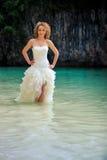 Blondynki panna młoda w puszystych rękach na talii w płytkim lazurowym morzu Zdjęcia Royalty Free