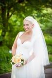 Blondynki panna młoda z ślubnym bukietem Zdjęcie Royalty Free