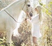 Blondynki piękna kobieta dotyka mejestic konia Fotografia Royalty Free