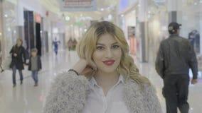 Blondynki sławna kobieta przy centrum handlowym bawić się z jej włosy i pozuje dla jej ogólnospołecznych środków rozlicza przed r zdjęcie wideo