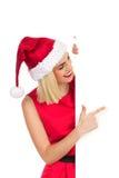 Blondynki Santa dziewczyna wskazuje przy plakatem Fotografia Royalty Free
