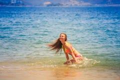 Blondynki szczupła gimnastyczka w bikini kucnięciach ono uśmiecha się w lazurowym morzu Obraz Royalty Free