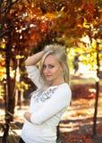 Blondynki wzorcowy ono uśmiecha się na jesieni tle zdjęcia royalty free