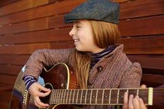 Blondynu dzieciaka dziewczyna bawić się gitarę z zima beretem Zdjęcia Royalty Free