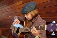 Blondynu dzieciaka dziewczyna bawić się gitarę z zima beretem Fotografia Stock