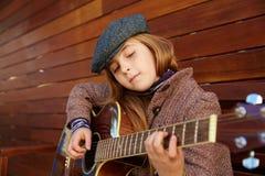 Blondynu dzieciaka dziewczyna bawić się gitarę z zima beretem Obrazy Stock