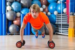 Blondynu mężczyzna gym pchnięcia pushup dumbbells Fotografia Stock