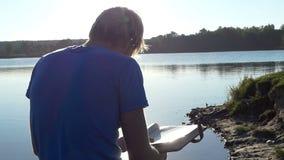 Blondynu mężczyzna spojrzenia przy jego photoalbum na jeziornym banku zbiory