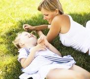 Blondyny matkują z córką ma zabawę na trawie, szczęśliwa rodzina, li Obrazy Royalty Free