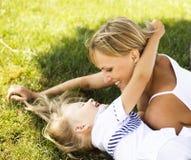 Blondyny matkują z córką ma zabawę na trawie, szczęśliwa rodzina, li Obraz Royalty Free
