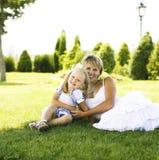 Blondyny matkują z córką ma zabawę na trawie, szczęśliwa rodzina, li obraz stock