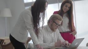 Blondyny obsługują w szkłach siedzi w lekkim wygodnym biurze z netbook przy stołem wyjaśnia jego pomysł koledzy zbiory wideo