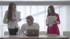 Blondyny obsługują w szkłach siedzi w lekkim wygodnym biurze z netbook przy stołowymi podpisywanie dokumentami które koledzy zdjęcie wideo