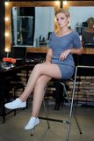Blondyny z długimi nogami w beżowym jedwabiu ubierają obsiadanie na czarnym karle zdjęcia royalty free