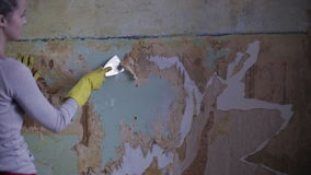 Blone woman removing old wallpaper. From the wall stock video footage