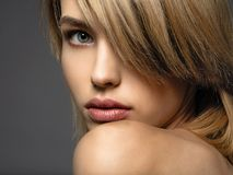 Blone woman with a short hair, fringe. blonde woman. Attractive blond model with blue eyes. Fashion model with a smokey makeup. Closeup portrait of a pretty royalty free stock photography