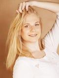 年轻凉快的blong十几岁的女孩弄乱了她的头发 免版税库存图片