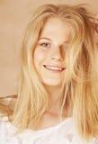年轻凉快的blong十几岁的女孩弄乱了她头发微笑 免版税图库摄影