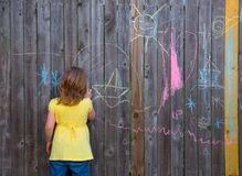 Blonk kid girl playing with drawing chalks in the backyard Stock Images