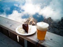 Blont öl och en skiva av Sachertorte, berg, vaggar och clouen arkivfoto