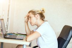 Blont arbete för trött kvinna på bärbara datorn hemma Henne ` s som fokuseras på arbete Frilans hemmastatt begrepp för arbete arkivfoto