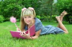 blont barn för kvinna för bokparkavläsning Arkivbild