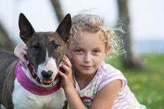 Blont barn med en bull terrier Arkivfoton