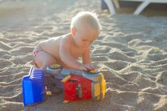 Blont behandla som ett barn att spela med leksakbilen på stranden arkivfoton