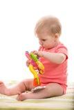 Blont behandla som ett barn flickan som spelar med blommaleksaken arkivbild