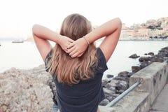 Blont Caucasian anseende för tonårs- flicka på seacoasten Arkivbilder