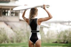 Blont flickaanseende för bakre sikt med wakeboarden på hennes huvud royaltyfria bilder