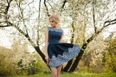 Blont flickaanseende på den körsbärsröda blomningen i trädgård under ett blommande träd royaltyfria bilder