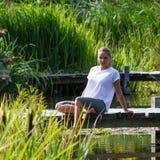 blont flickasammanträde för 20-tal på ponton med fot i vatten Arkivfoton