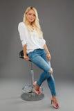 Blont flickasammanträde på den bärande jeansen för stol och den vita skjortan Royaltyfri Bild