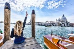 Blont flickasammanträde på pir i Venedig tillbaka sikt Arkivfoton