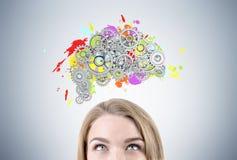 Blont huvud och hjärna för kvinna s med kugghjul arkivfoto