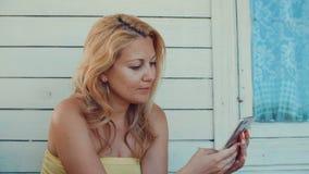 Blont kvinnamaskinskrivningmeddelande vid mobiltelefonen och vila på sommarterrass arkivfilmer