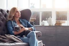 Blont kvinnasammanträde med katten på soffan arkivfoto
