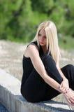 Blont kvinnasammanträde på den låga väggen som bär en svart halsjumpsuit Royaltyfria Bilder