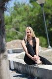 Blont kvinnasammanträde på den låga väggen som bär en svart halsjumpsuit Royaltyfria Foton
