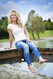 Blont kvinnasammanträde på en brygga Royaltyfri Bild