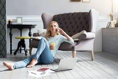 Blont kvinnasammanträde på golv och samtal per telefonen royaltyfria bilder