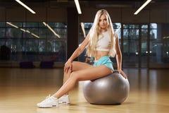 Blont kvinnasammanträde på schweizareboll Royaltyfria Bilder
