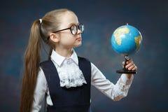 Blont litet jordklot för skolflickahållvärld i hand royaltyfri bild