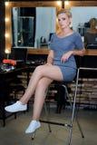Blont med långa ben i beige siden- klänningsammanträde på den svarta fåtöljen royaltyfria foton